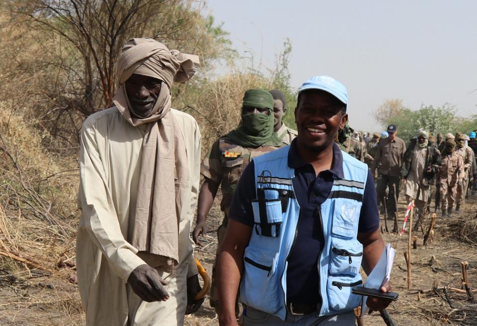 A Humanitarian Coordinator in a UN vest and cap walks alongside a tall man in a dusty-white robe through the bush.