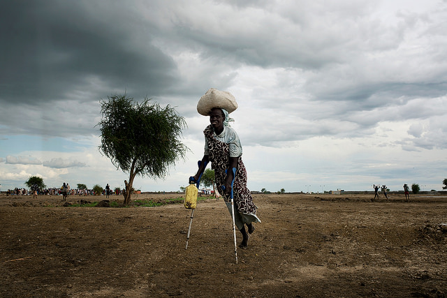A woman with disability carrying relief items and walking with crutches in the middle of the field,keeping social distance.