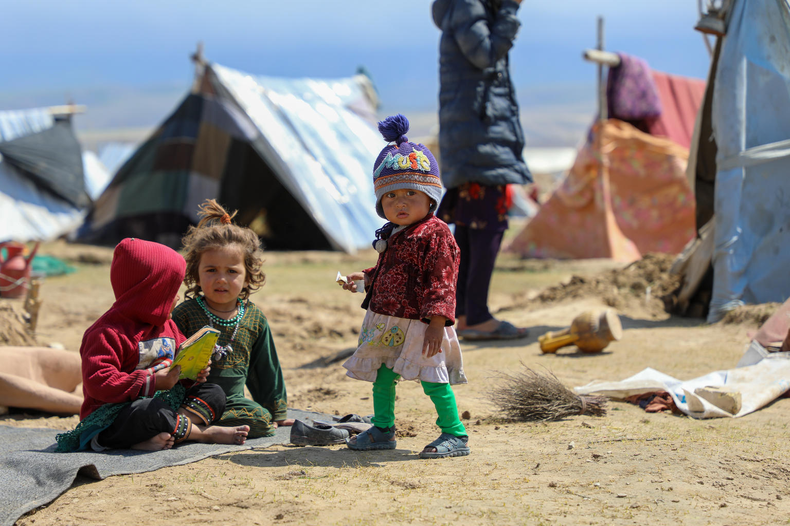 3 kids (2-3 years old) wearing winter cloth in a camp setting.