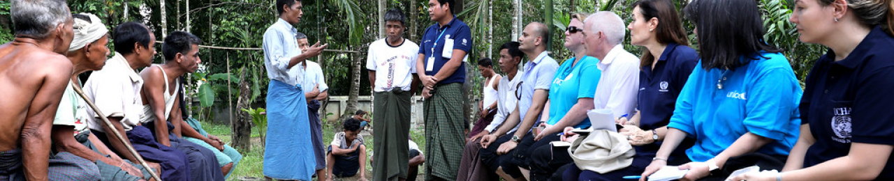 Two groups of people sit on opposing benches, UN delegates on the right and locals on the left. A local and a UN delegate are standing between them, wearing longyi - a cloth wrapped around their torso, a traditional garment.