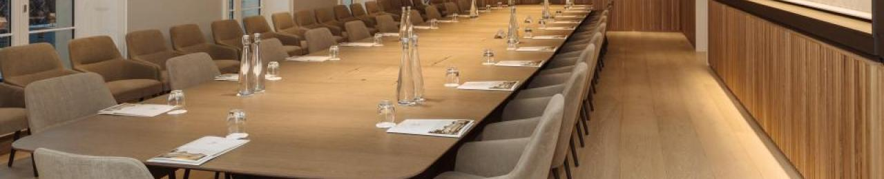 Glasses, water, and document packs are arranged neatly around a long wooden table, ready for meeting participants.