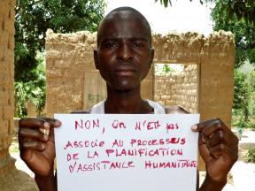 A man holds up a sign which reads, in French, 'No, we are not consulted in the planning of humanitarian assistance'.