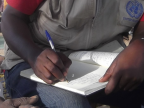 An image of a man wearing a UN jacket writing in a large notebook.