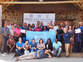 A group of people gather round a UN flag at a training course, in front of a sign which reads 'UNDAC induction course'.