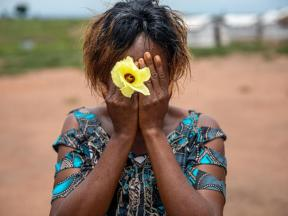 dark-skinned young girl covering her face and holding a flower - cover for the CERF GBV fund release