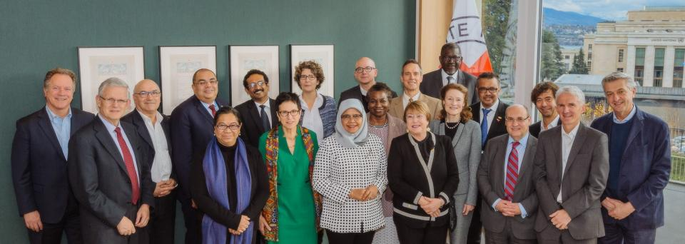 A staged group photo of the IASC Principals in front of an ICRC flag and a window with the UN Geneva HQ visible.
