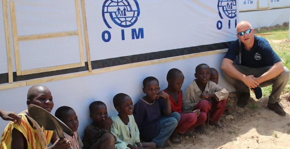 A photo of IOM Deputy Director of Operations and Emergencies next to a group of boys sat in front of an IOM shelter.