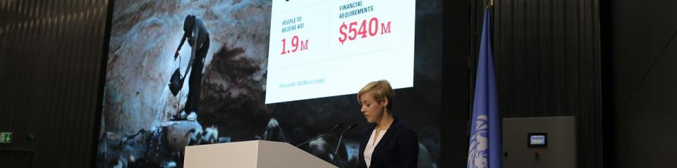 A banner photo of a woman speaking in front of a screen which reads 'People to receive aid: 1.9M and Financial Requirements $540M'.