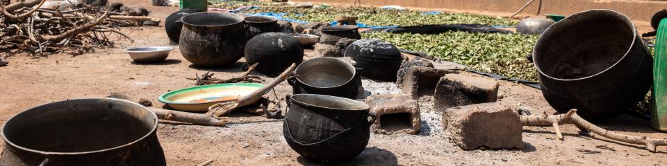 A group of large pots lie strewn across the dirt.