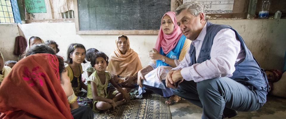 High Commissioner Filippo Grandi talks to a family of vulnerable Rohingya refugees at Kutupalong camp in Cox's Bazar, Bangladesh. They are sat round a rug, with a blackboard visible in the background - apparently a classroom.