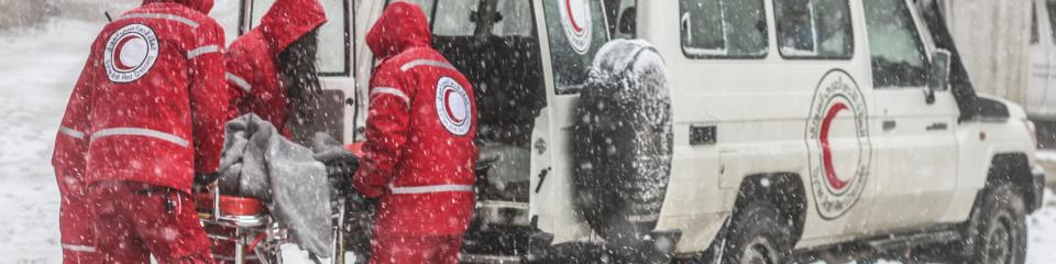 Four Syrian Red Crescent staff, wearing winter jackets with the hood pulled up, lift a stretcher into the back of a Red Crescent landrover during a snowstorm.