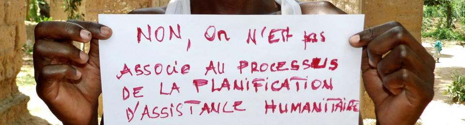 """An image a person holding up a piece of paper with """"non, on n'est pas associe au processus de la planification d'assistance humanitaire"""" - """"We are not consulted in the plannning of humanitarian assistance""""."""