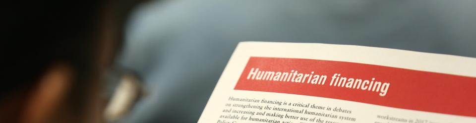 """A man reading a paper which reads """"Humanitarian financing. Humanitarian financing is a critical theme in debates on strengthening the international humanitarian system and increasing and making better use of the ... available for humanitarian..."""""""