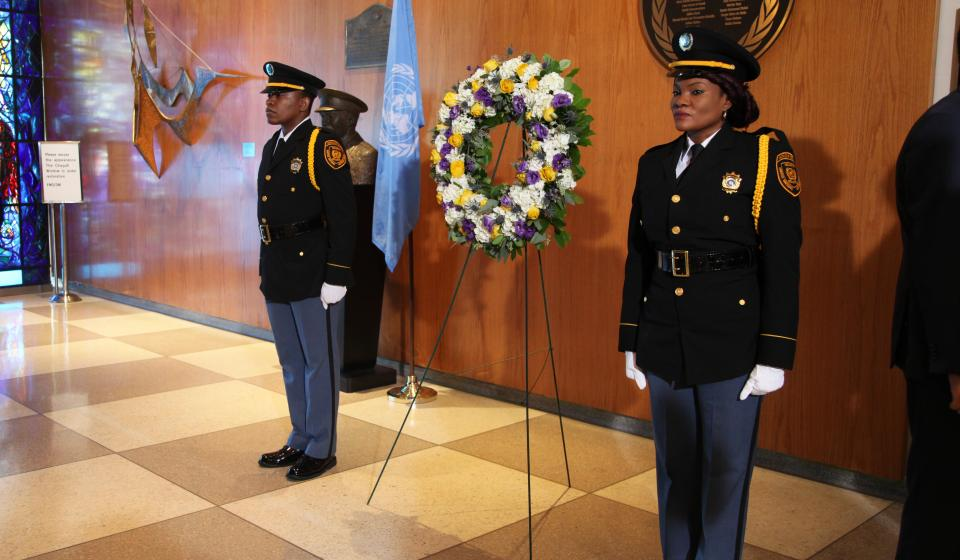 A photo of a wreath flanked by two uniformed people.